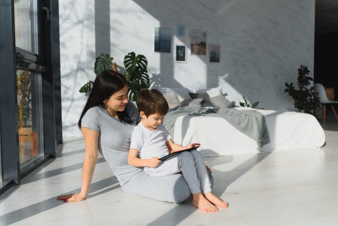 Crianças estão mais dependentes dos pais e das telas, diz estudo Datafolha; garoto usa tablet e está no colo da mãe dentro de uma casa