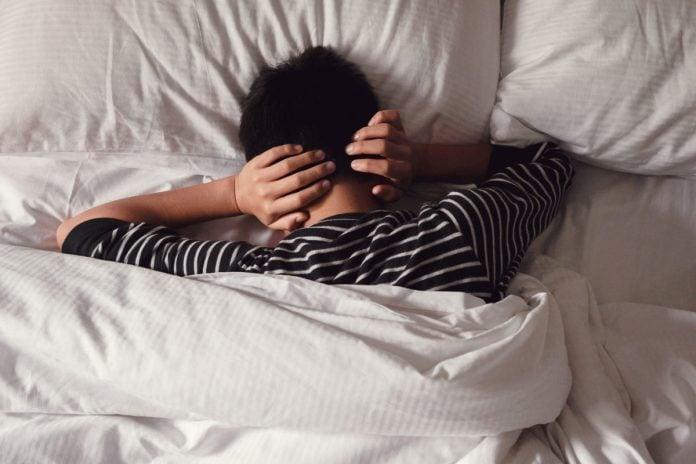 'Estresse tóxico': 52% das crianças tiveram o sono prejudicado na pandemia; menino está deitado na cama de barriga para baixo e com mãos sobre a nuca