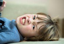 Criança que não aceita regras e se opõe a tudo? Pode ser o Transtorno Opositor Desafiador (TOD); menino está deitado no chão e tem cara de raiva