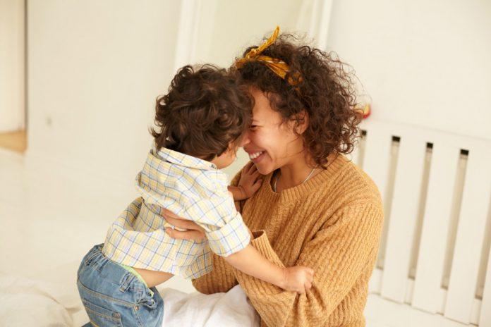 Uma mãe que aprendeu o significado do toque físico; mãe encosta testa na testa do filho e o segura debaixo dos braços