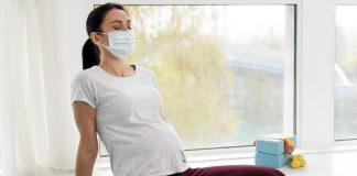 Grávidas sem comorbidades podem se vacinar contra Covid-19 em SP; grávida de máscara está sentada em colchonete