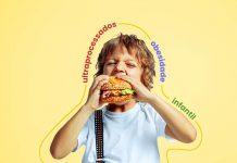 Alimentos ultraprocessados na infância pioram obesidade na vida adulta; menino de camiseta branca e suspensório dá mordida em um sanduíche de hambúrguer
