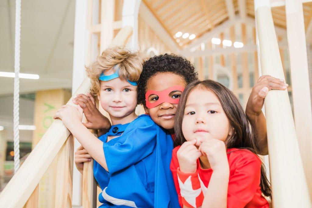 Brincadeiras que ajudam as crianças a desenvolverem suas capacidades; tres crianças estão fantasiadas de super-herois