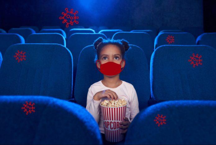 Cinema nas férias: dá para levar as crianças com segurança?; menina de máscara está sentada em poltrona de sala de cinema