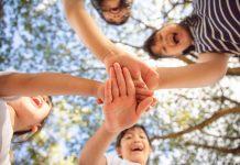 Trabalho voluntário: uma experiência única para quem o pratica; crianças apoiam mãos uma sobre outra em área ao ar livre, foto foi tirado debaixo para cima