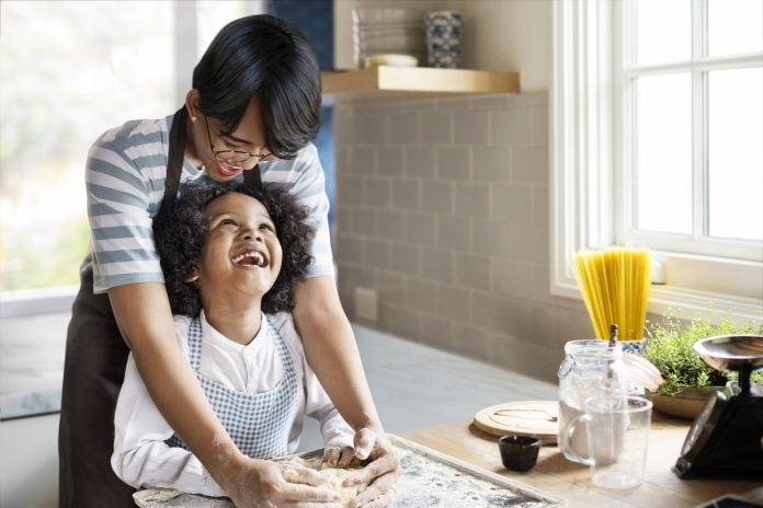 O desafio para os pais de criar filhos sem o machismo; pai está atrás do filho e ambos mexem em farinha de pão sobre tábua
