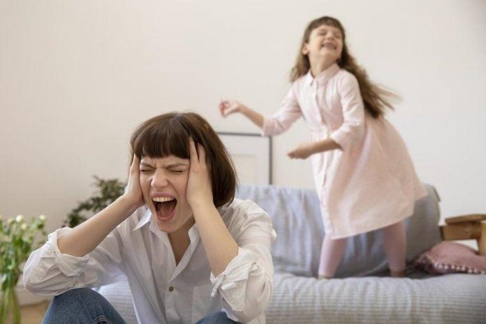 Os gritos dos pais: alguns dos motivos que levam a isso; mãe grita com mãos na cabeça e filha aparece ao fundo rindo