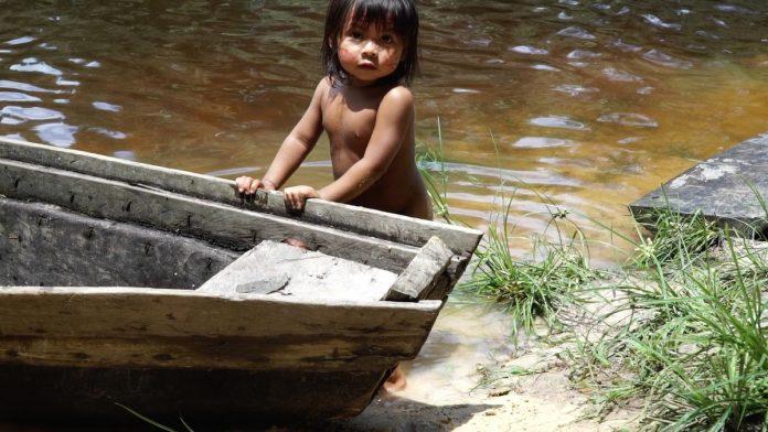 Para assistir online: a infância de povos indígenas em 6 curtas-metragens; menina índia apoia mãos sobre barco na beira de um rio, cena do curta