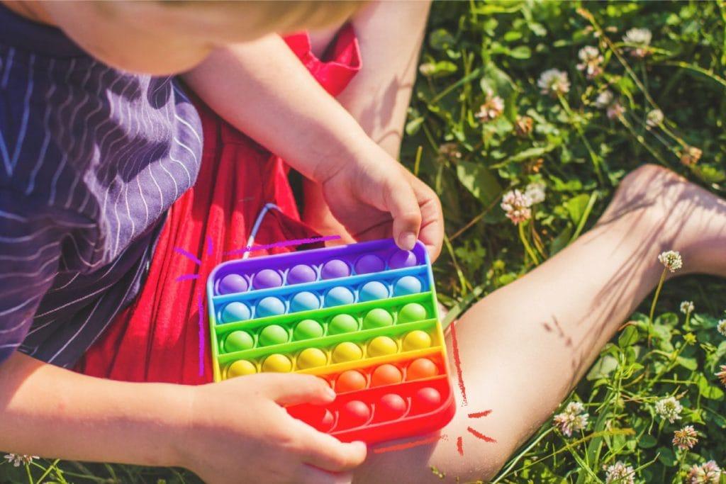"""Fidget toy: o brinquedo do momento que estimula o bem-estar; criança pequena brincando com o """"Bubble Fidget Toy"""""""