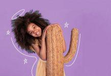 Pais não devem exigir dos filhos que sejam perfeitos; menina sorridente de cabelo crespo apoia braços sobre cacto marrom claro