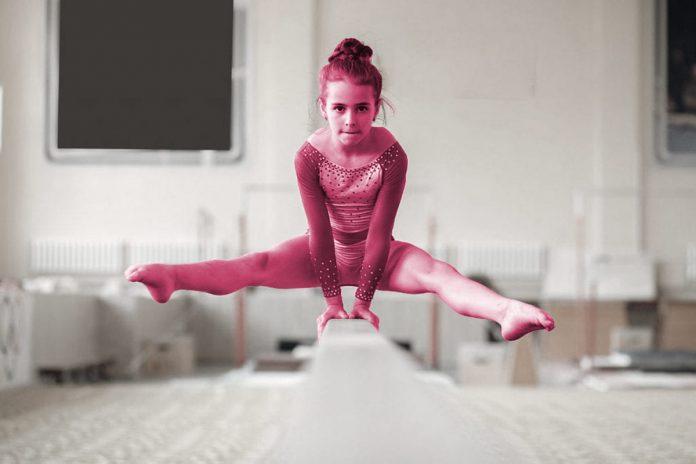 O fracasso e o sucesso dos filhos: como os pais reagem a isso; menina pratica ginástica olímpica na barra e tem pernas abertas em