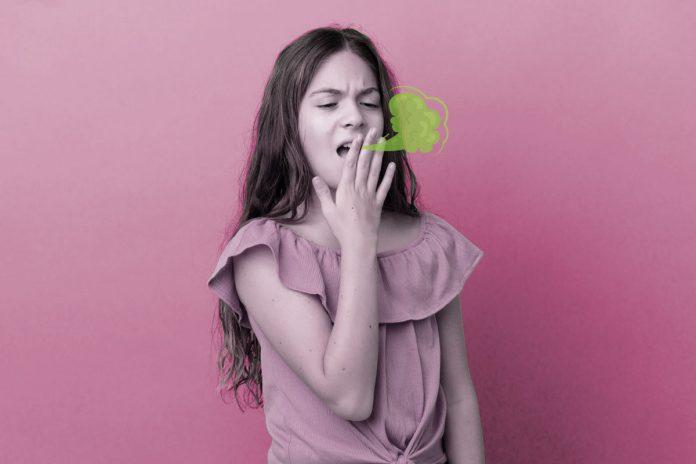 Criança com mau hálito: causas e formas de reduzir o cheiro forte na boca; menina de blusa rosa tem mão sobre boca aberta