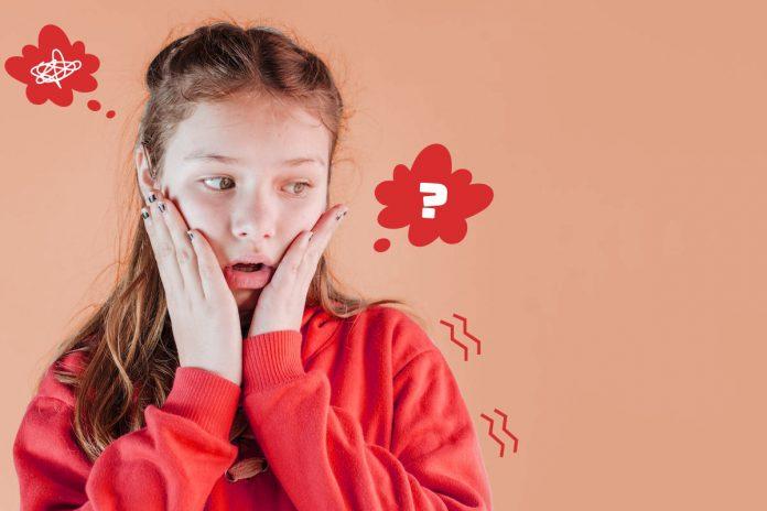 Puberdade precoce: saiba as razões e como agir com seu filho; menina de casaco laranja tem mãos sobre bochechas e olha para o lado assustada