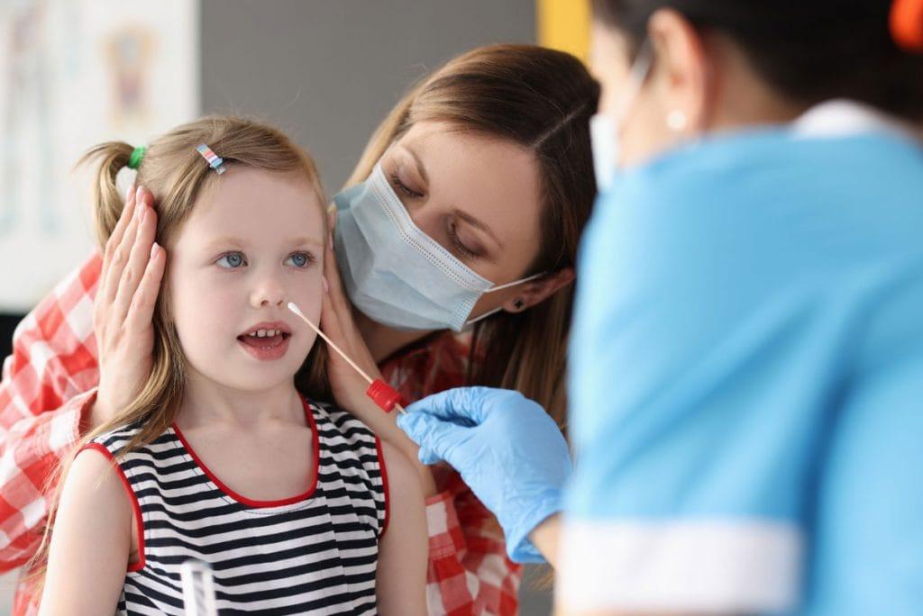 Teste de Covid-19 em criança: o que considerar para realizar o exame; menina sorridente segura teste de Covid-19; mãe acompanha filha que faz teste de Covid - médico coloca cotonete em sua boca para coleta de saliva