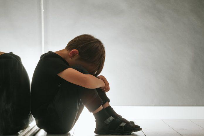 130 mil crianças perderam pais, avós ou cuidadores para a Covid-19; menino sentado no chão encosta cabeça e abraça joelhos com os braços