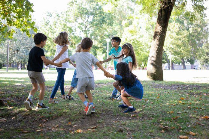 Contato com a natureza beneficia a saúde física e mental das crianças; crianças brincam de mãos dadas em roda em área verde ao ar livre
