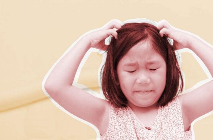 Volta às aulas: atenção ao aumento de doenças como piolho e impetigo; menina oriental coça a cabeça com as mãos