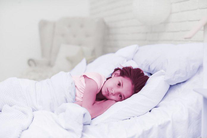 Insônia infantil: quais são as causas e como tratar? Criança deitada na cama com os olhos abertos
