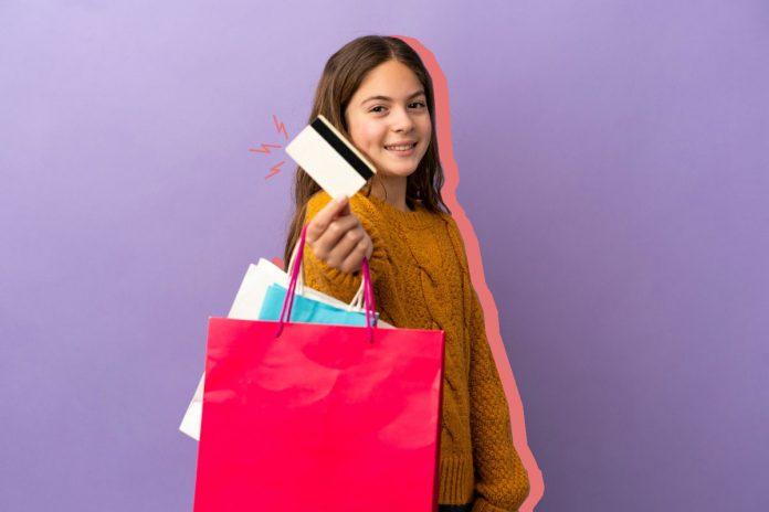 A importância da mesada para a educação financeira das crianças; menina sorrindo segurando um cartão de crédito preto e branco com duas sacolas penduradas no braço, uma azul e outra rosa