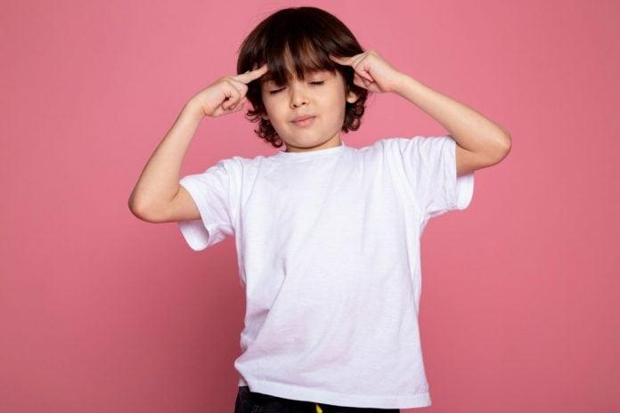 Saiba identificar a mentalidade que seu filho desenvolve; menino de olhos fechados apoia dedos sobre laterais da testa