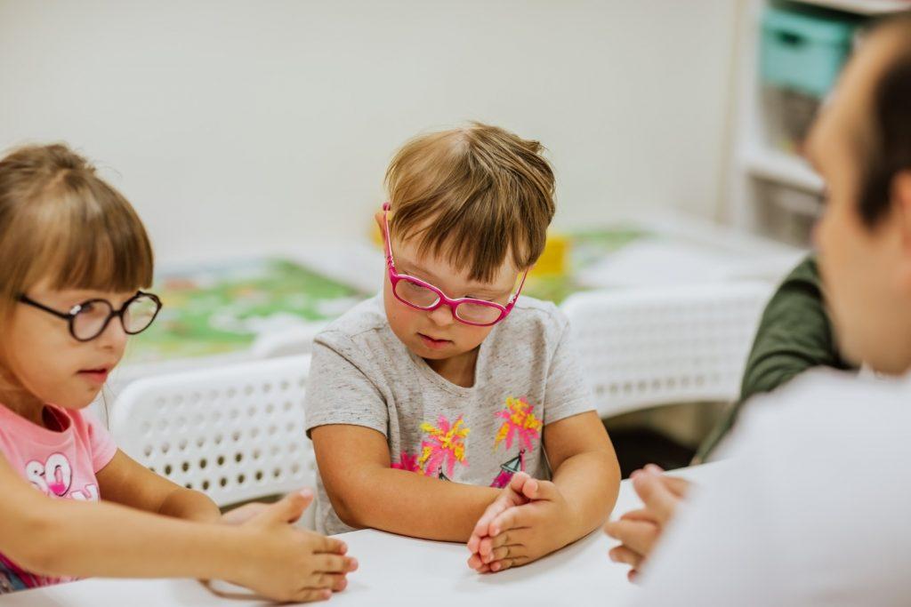 """Ministro da Educação diz que as crianças com deficiência """"atrapalham""""; crianças com síndrome de down usando óculos coloridos sentados em frente a uma mesa brincando"""