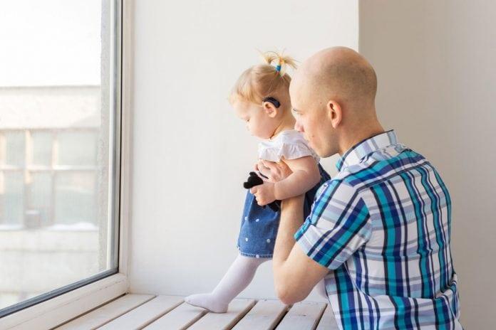 Paternidade atípica: pais de filhos com deficiência buscam maior participação paterna no debate sobre inclusão; Pai segura filha, que usa aparelho auditivo, no colo para olharem a janela