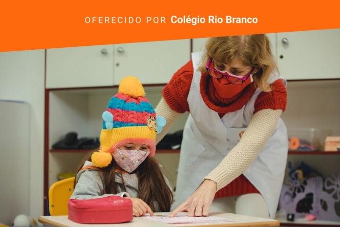 Alfabetização: como ajudar seu filho com a 'pega' do lápis e a letra cursiva; professora de máscara mostra algo em atividade de aluna que está de máscara e gorro no papel