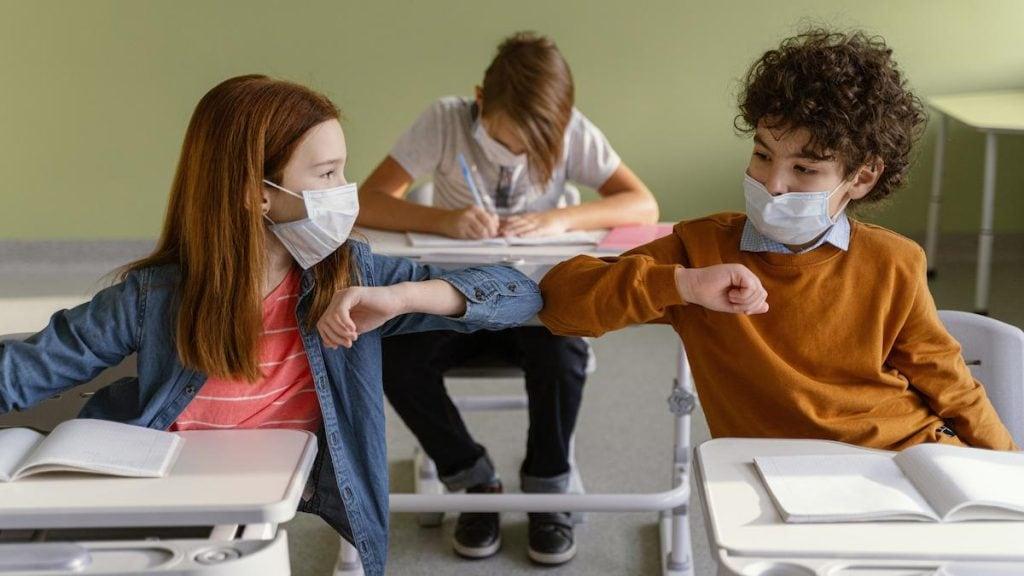 Volta às aulas: ações práticas para garantir a aprendizagem das crianças; alunos na sala de aula se cumprimentam com cotovelos