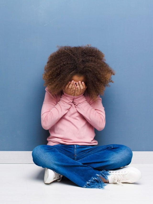 Como melhorar a saúde mental das crianças; menina com as mãos cobrindo o rosto
