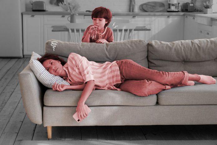 Passar um tempo sem os filhos é necessário, dizem especialistas; mãe cansada deitada no sofá segurando um celular com criança soprando um apito ao fundo