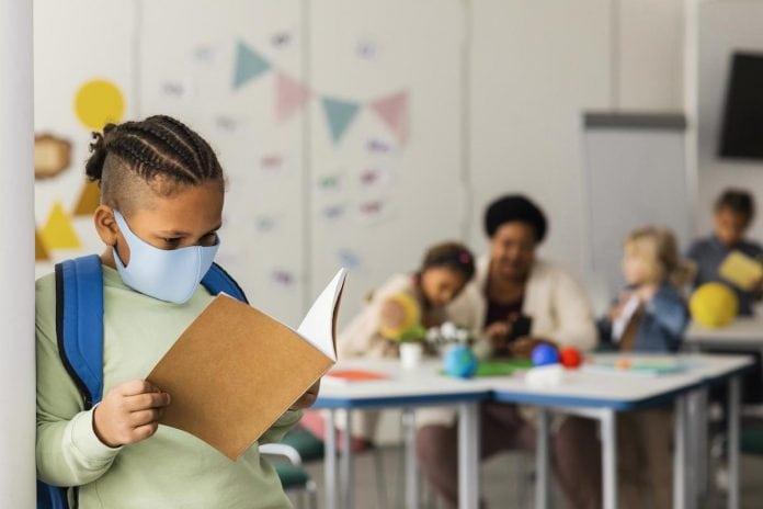 Mãe e especialista em vírus fala sobre volta às aulas com a variante Delta; garoto de máscara lê livro em pé na sala de aula