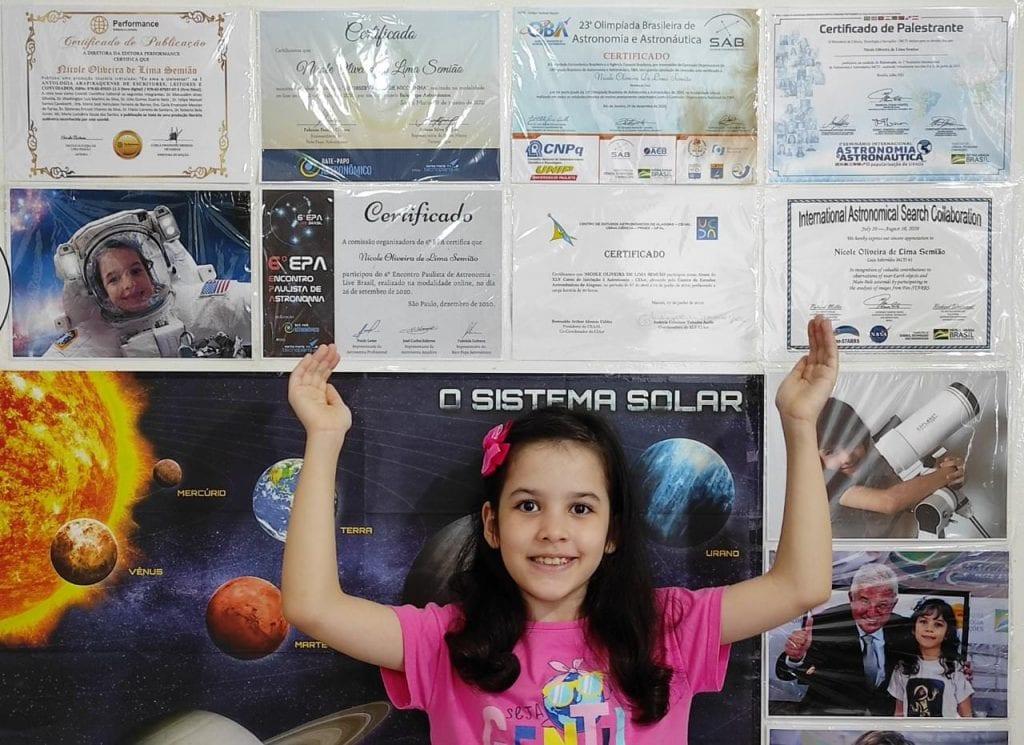 Nicole Oliveira, prodígio de astronomia de 8 anos, já detectou 7 asteroides; Nicole com um pôster do sistema solar e seus certificados de astronomia colados na parede