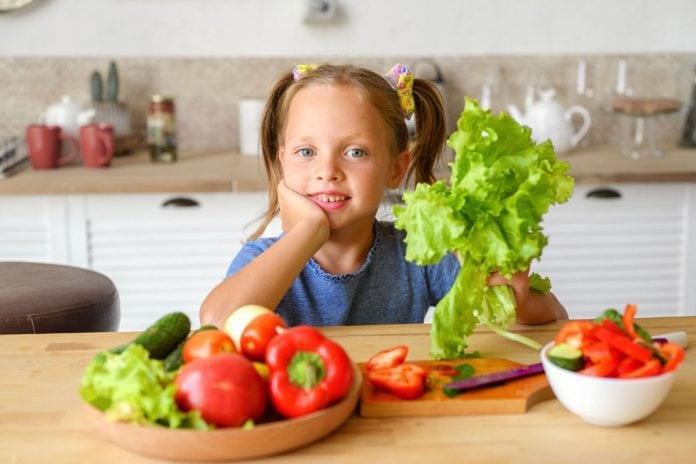 Dieta plant-based é alternativa saudável para alimentação das crianças; Menina de blusa azul segurando uma alface em uma das mãos, sentada à mesa com um recipiente com vegetais no canto esquerdo da imagem.