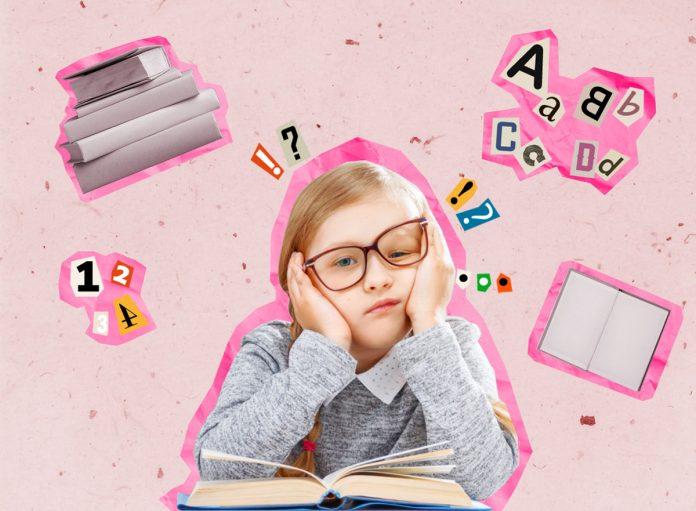 As dificuldades e habilidades das crianças com dislexia; criança com óculos com a cabeça entre as mãos com uma expressão confusa apoiando os cotovelos sobre um livro aberto; Criança com óculos com a cabeça entre as mãos com uma expressão confusa apoiando os cotovelos sobre um livro aberto