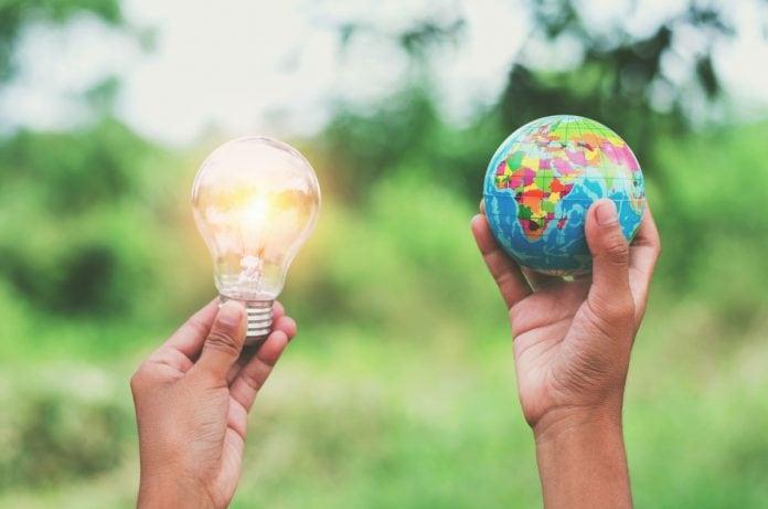 Consumo consciente de energia deve fazer parte da rotina das crianças; ; duas mãos segurando uma lâmpada acesa e um globo