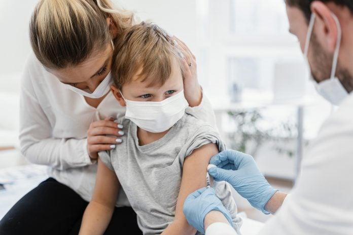 Chile aprova a vacina CoronaVac para crianças com mais de 6 anos; médico com máscara e luvas azuis aplicando vacina em criança pequena no colo da mãe, os dois também usam máscara