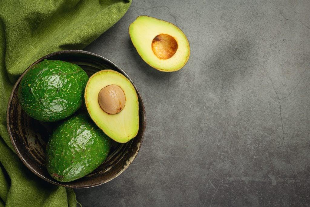 13 alimentos superpoderosos para a saúde das crianças; abacates em cima de um pote preto em um fundo escuro, há um abacate aberto com a semente dentro do pote, sua outra metade está sob o fundo preto