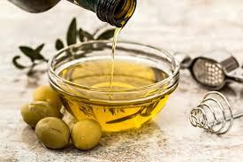 13 alimentos superpoderosos para a saúde das crianças; garrafa despejando azeite de oliva em um pote de vidro cheio, ao redor encontram-se azeitonas e folhas