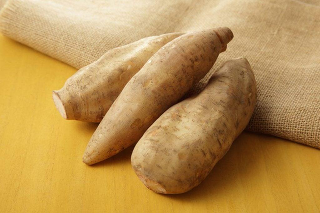 13 alimentos superpoderosos para a saúde das crianças, três batatas-yacon em cima de um saco marrom sobre um fundo amarelo