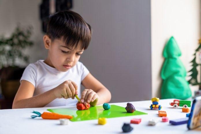 Dicas de atividades para aproveitar o Dia das Crianças em família; criança brincando com massinha na mesa