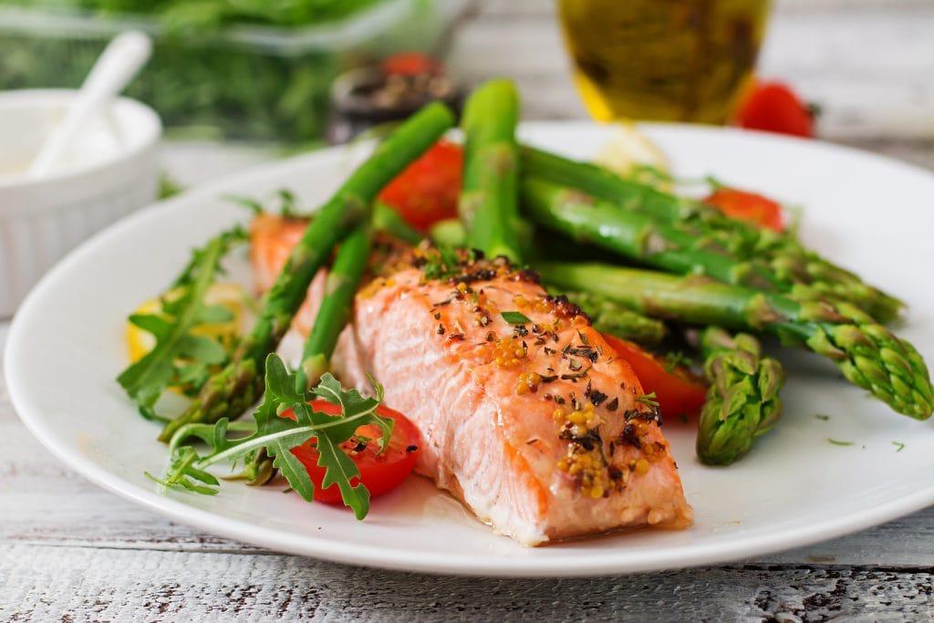 13 alimentos superpoderosos para a saúde das crianças; salmão grelhado em um prato com ervas, aspargos e tomates