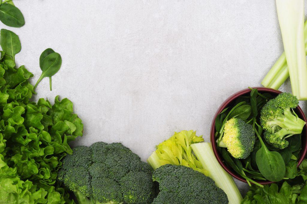 13 alimentos superpoderosos para a saúde das crianças; alface, espinafre, brócolis e outros vegetais verdes sob um fundo branco